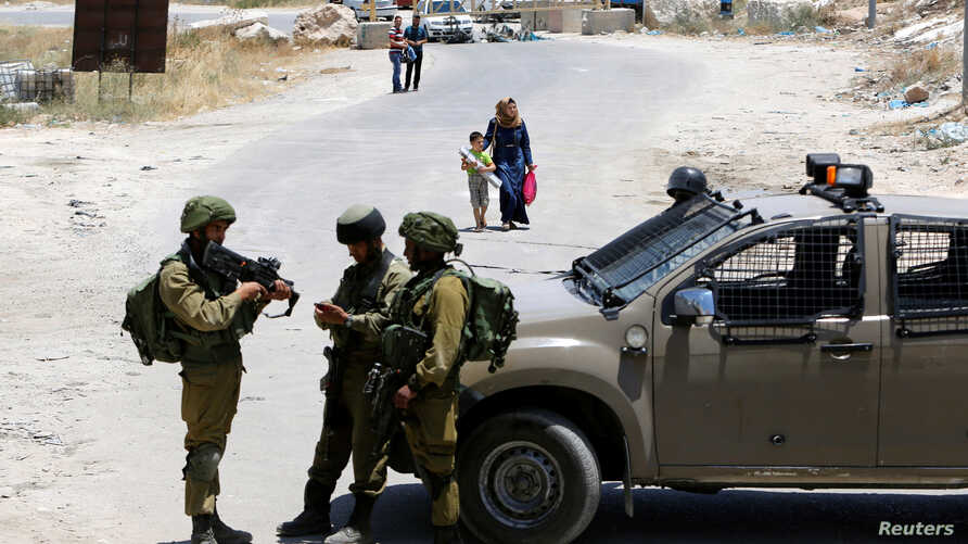 Israeli soldiers stand guard at the entrance of Yatta near the West Bank city of Hebron, June 9, 2016.