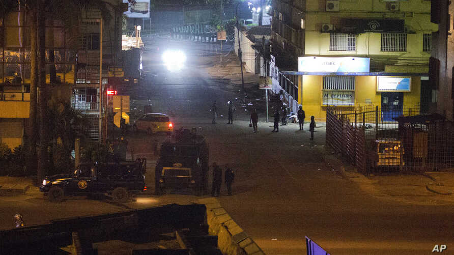 Congolese riot police take position around the electoral commission building at night in Kinshasa, Congo, Tuesday Jan. 8, 2019.