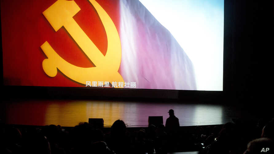 """In this Thursday, March 22, 2018 photo, the state-backed documentary film """"Amazing China"""" shows the Communist party flag and subtitles in Chinese """"In the wind and rain, the voyage is magnificent"""" at the Beijing Film Academy in Beijing, China."""
