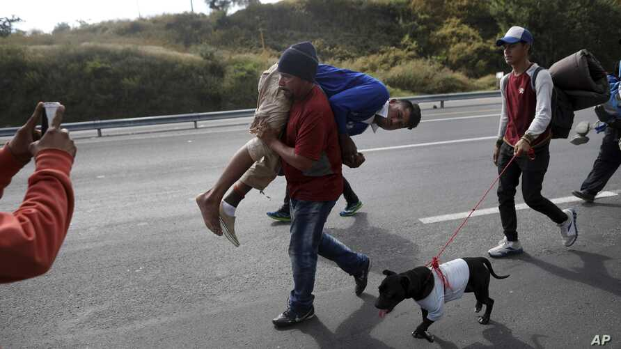 Migrant Darwin Leonel Carcamo is carried by a fellow migrant, part of the caravan hoping to reach the U.S. border, after he fell off a truck and broke his leg, on the road that connects Irapuato with Guadalajara, Mexico, Nov. 12, 2018.