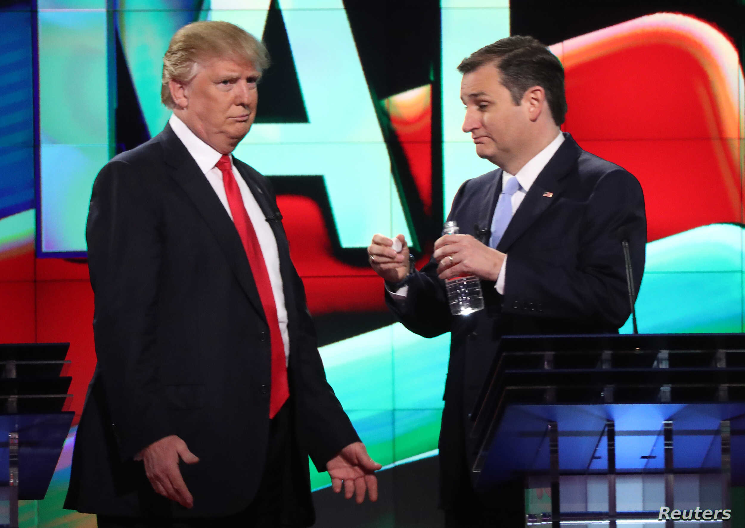 Republican U.S. presidential candidate Donald Trump (L) talks with rival Ted Cruz during a commercial break in the midst of the Republican U.S. presidential candidates debate sponsored by CNN at the University of Miami in Miami, Florida, March 10, 20