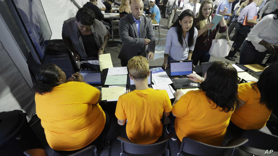 FILE - Job candidates are processed during a job fair at the Amazon fulfillment center in Robbinsville Township, N.J., Aug. 2, 2017.
