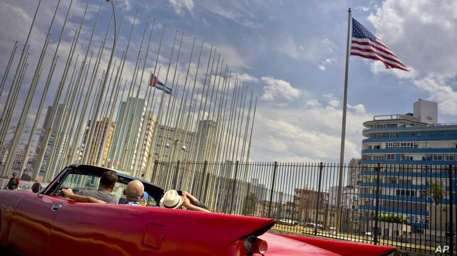 Tourists ride a vintage American convertible as they drive next to the American flag and a Cuban flag at the United States embassy in Havana, Cuba, March 18, 2016.