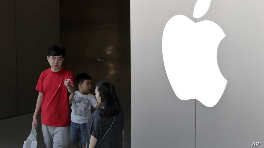 FILE - A Chinese family walks out of an Apple store in Beijing, July 30, 2017. Hundreds of workers protested Wednesday night, Oct. 18, 2017, over bonuses promised through labor brokers who recruited them to work at Jabil Inc.'s Green Point factory, a