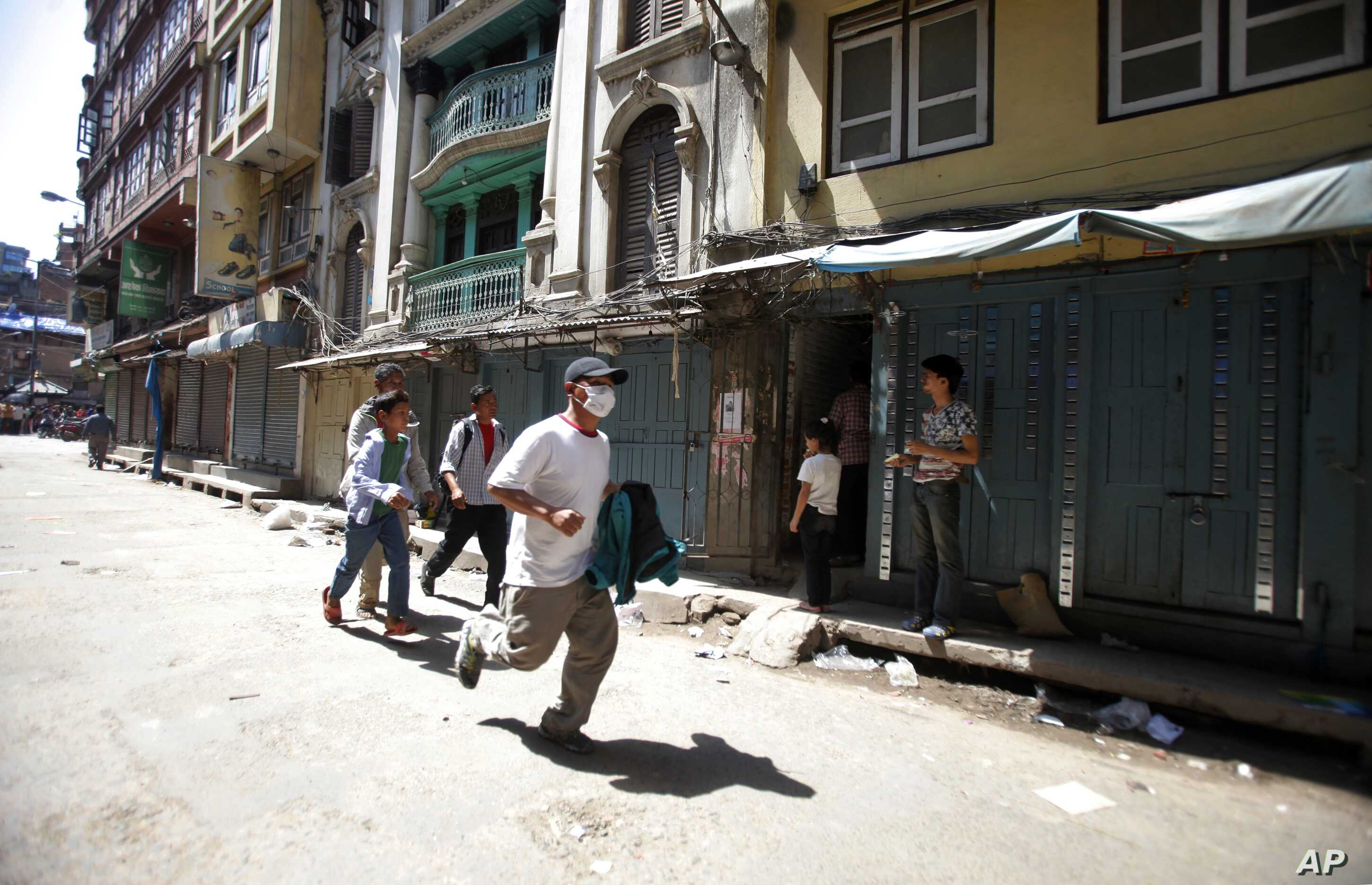 A Nepalese man runs to safety after a second earthquake hit Nepal in Kathmandu, Nepal, Tuesday, May 12, 2015. A major earthquake hit a remote mountainous region of Nepal on Tuesday, triggering landslides and toppling buildings less than three weeks a