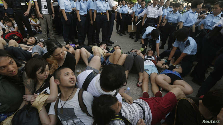 Protesters join hands as they look at fellow protesters being dragged away by the police on a street at Hong Kong's financial Central district after staying an overnight sit-in, July 2, 2014.
