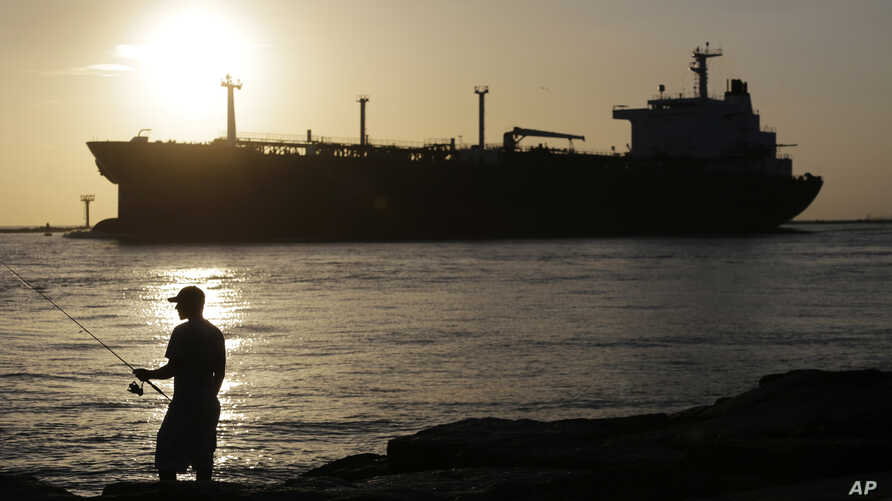FILE - An oil tanker passes a fisherman as it enters a channel near Port Aransas, Texas, July 21, 2015, heading for the Port of Corpus Christi. The U.S., seemingly awash in crude oil after an energy boom sent thousands of workers scurrying to the pla