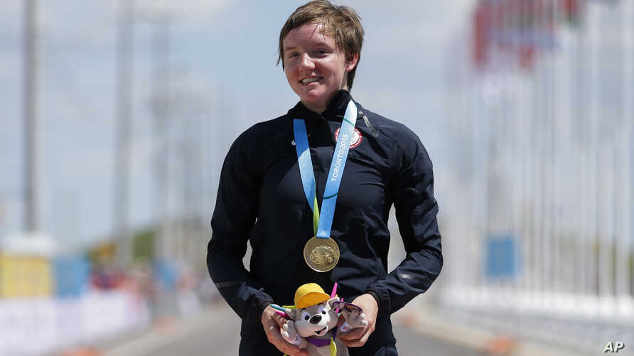 In this Wednesday, July 22, 2015 file photo, United States gold medalist Kelly Catlin poses after winning  the women's individual time trial cycling competition at the Pan Am Games in Milton, Ontario.