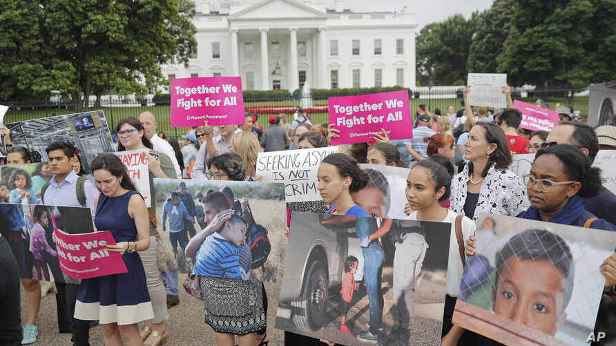 People hold up signs and photographs during a  demonstration opposed to the White House policy that separated more than 2,300 children from their parents over the past several weeks in front of the White House in Washington, June 21, 2018.