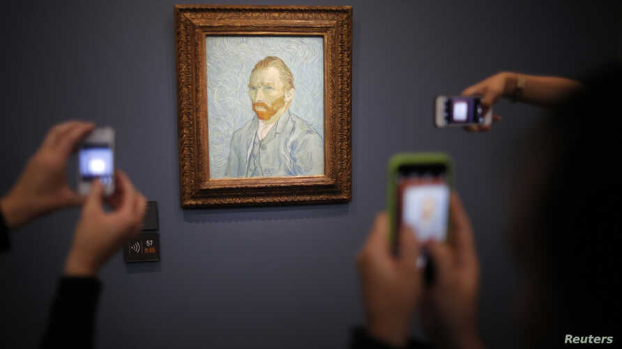 "FILE - Visitors take pictures with their mobile phones of the painting ""Portrait de l'Artiste, 1889"" (Self-Portrait) by artist Vincent Van Gogh (1853-1890) at the Musee d'Orsay in Paris,  July 28, 2015."
