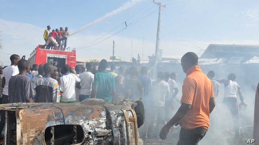 People gather at the scene of a car bomb explosion at the central market, Maiduguri, Nigeria, July 1, 2014.