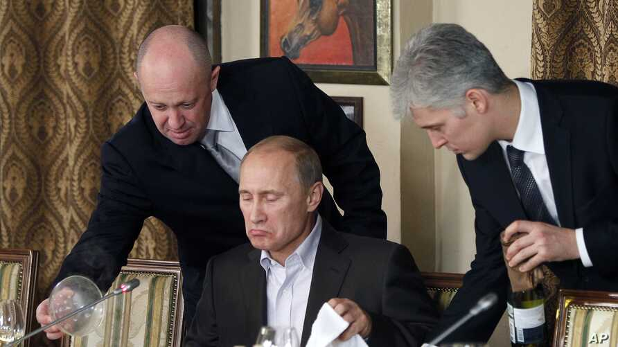 FILE - In this Nov. 11, 2011, photo, businessman Yevgeny Prigozhin, left, serves food to Russian Prime Minister Vladimir Putin, center, during dinner at Prigozhin's restaurant outside Moscow, Russia.
