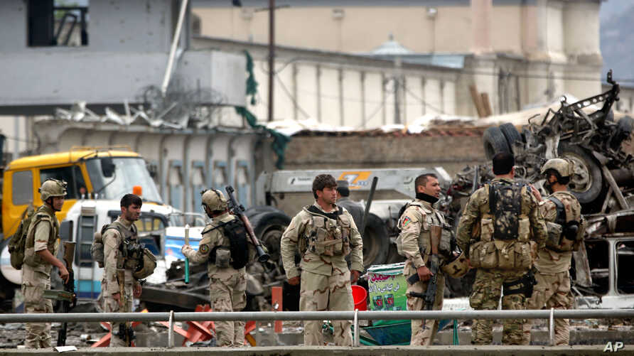 FILE - In this Tuesday, April 19, 2016 file photo, Afghan security forces inspect the site of a Taliban-claimed deadly suicide attack in Kabul, Afghanistan.