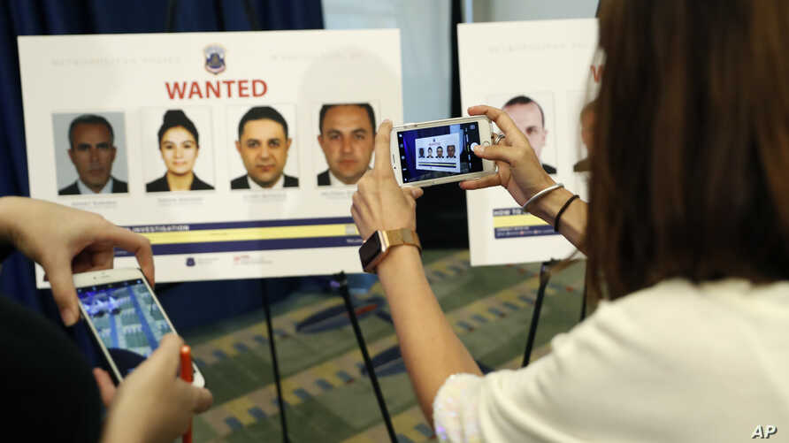 Reporters photograph wanted posters of people facing criminal charges before a news conference in Washington, June 15, 2017, about the May 16, 2017 altercation outside the Turkish Embassy in Washington during the visit of the Turkish president.
