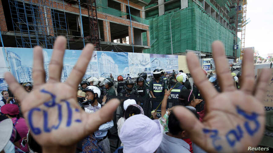 """A man, with his hands painted with words that translate to """"Release"""", demonstrate to demand the release of five opposition members of parliament, as police officers block a street near the Phnom Penh Municipal Court in central Phnom Penh, Cambodia, J"""