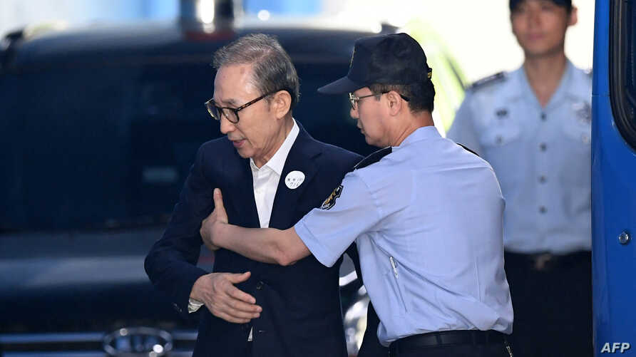 Former South Korean president Lee Myung-bak, left, is helped by a prison official as he arrives at a court to attend his trial in Seoul, Sept. 6, 2018.