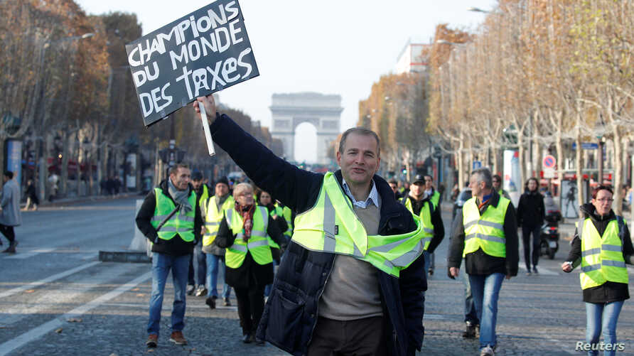 """A man wearing a yellow vest, a symbol of French drivers' protest against higher fuel prices, holds a placard with the message, """"World Champions in Taxes"""", as demonstrators gather on the Champs Elysees in Paris, France, Nov. 17, 2018."""