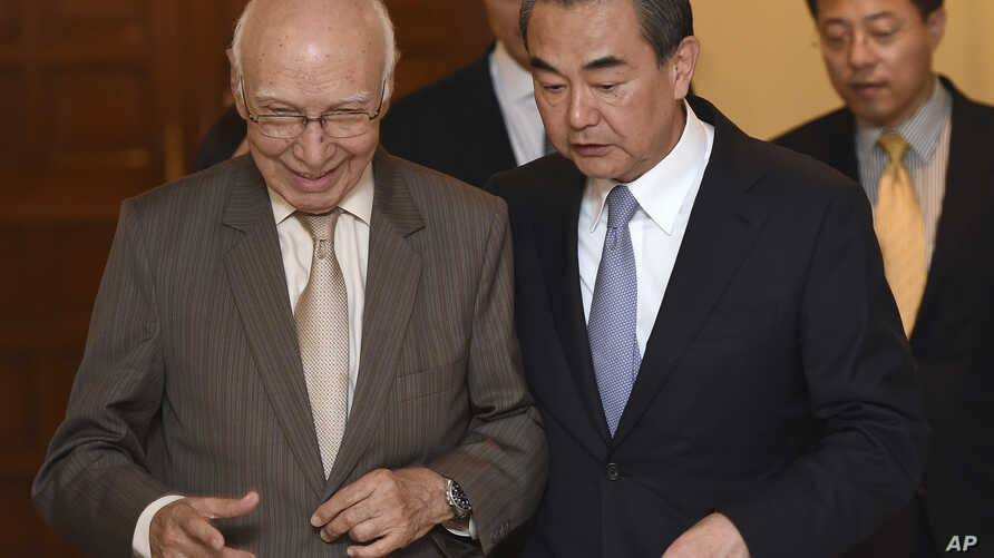 Visiting Chinese Foreign Minister Wang Yi, right, and Pakistan's adviser on foreign affairs Sartaj Aziz, left, leave after a press conference, in Rawalpindi, Pakistan, June 25, 2017.