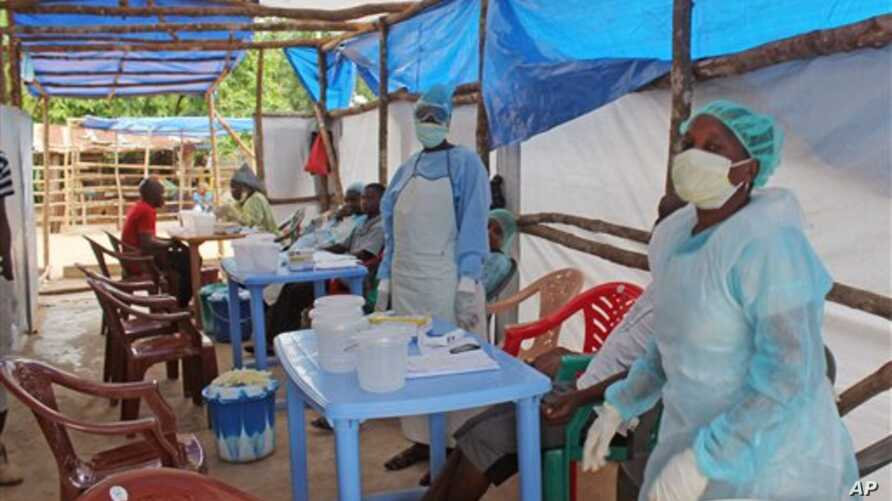 In this photo taken on Sunday, July 27, 2014,  Medical personnel inside a clinic taking care of Ebola patients in the Kenema District on the outskirts of Kenema, Sierra Leone.  Liberia President Ellen Johnson Sirleaf has closed some border crossings
