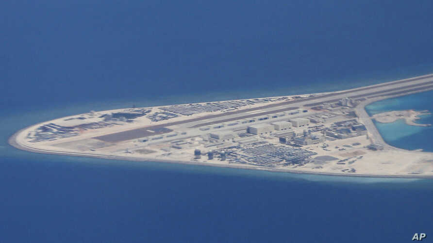 Chinese structures and an airstrip on the man-made Subi Reef at the Spratly group of islands in the South China Sea are seen from a Philippine Air Force C-130 transport plane of the Philippine Air Force, April 21, 2017. The South China Sea issue is e...