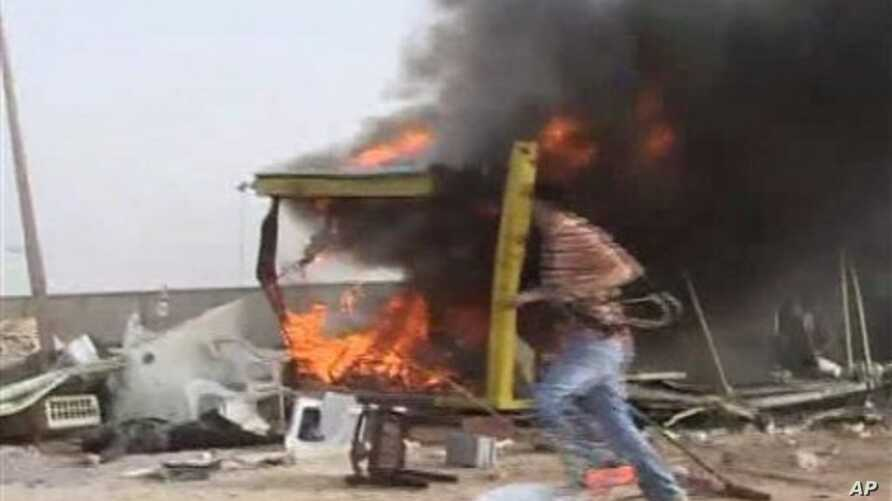In this image taken from Associated Press Television News footage an unidentified person runs away from a shelled checkpoint near the port area of Misrata, Libya, May 1, 2011