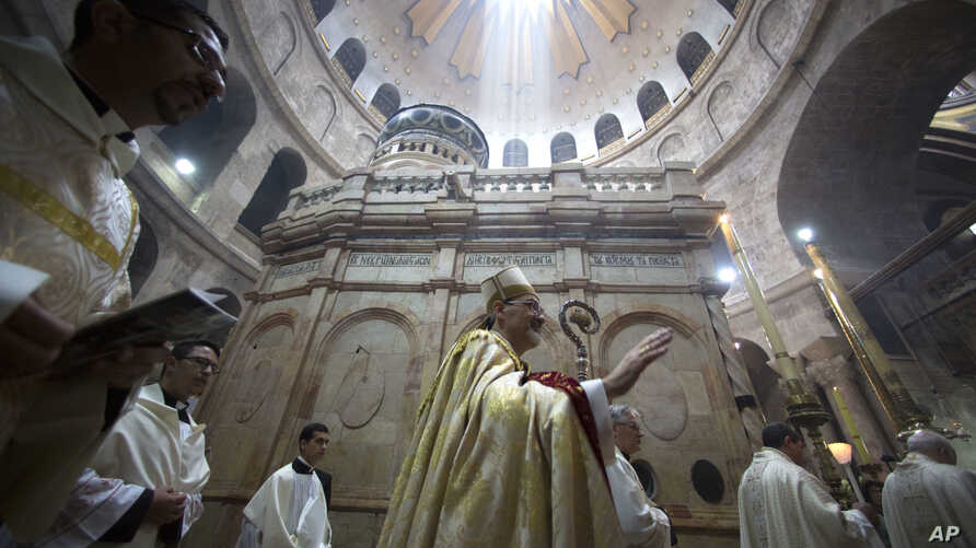 Latin Patriarch of Jerusalem Pierbattista Pizzaballa, center, walks with Christian clergymen holding candles during the Easter Sunday procession at the Church of the Holy Sepulchre in Jerusalem, April 16, 2017.