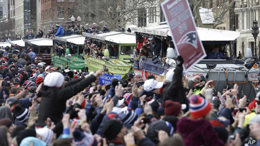 New England Patriots fans cheer as the team passes by in a procession of duck boats during a parade in Boston to honor the Patriots' Super Bowl XLIX victory over the Seattle Seahawks, Feb. 4, 2015.,