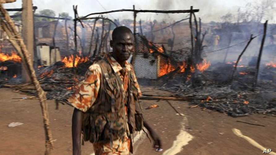 A policeman walks past the smouldering remains of a market in Rubkona near Bentiu in South Sudan, April 23, 2012.