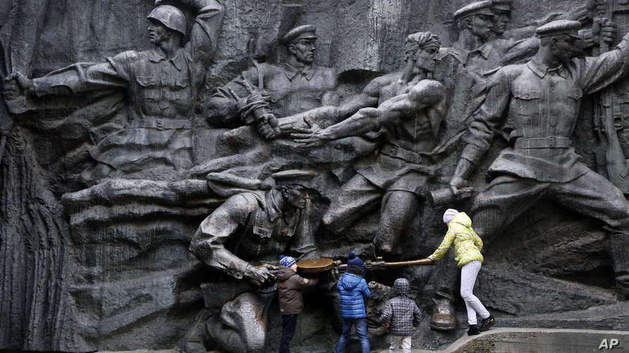 Children play at the monument of the Unknown Soldier, a memorial to World War II veterans, in a memorial park in Kyiv, Ukraine, Nov. 1, 2017.