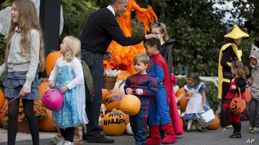 President Barack Obama pats a child dressed as Superman on the head during Halloween festivities near the South Portico of the White House in Washington, Friday, Oct. 31, 2014.