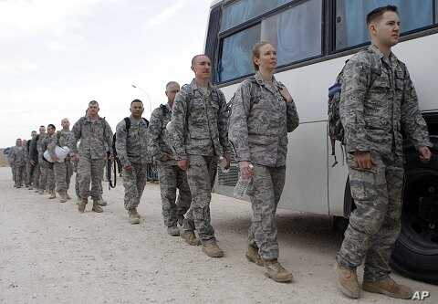 US service members queue to board a bus as they begin their journey home at al-Asad Air Base west of Baghdad, Iraq, November 1, 2011.