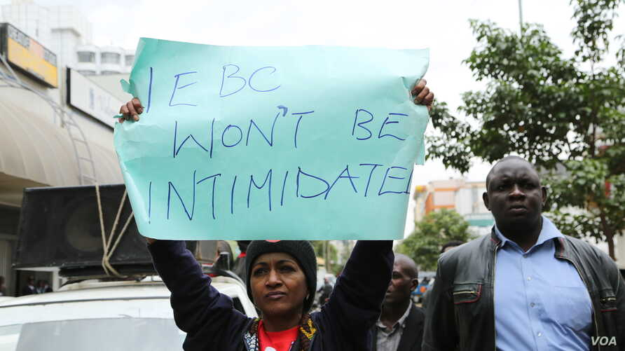Protesters hold signs like this one, which demands an end to the intimidation of election officials, during a march in Nairobi, Aug. 1, 2017.