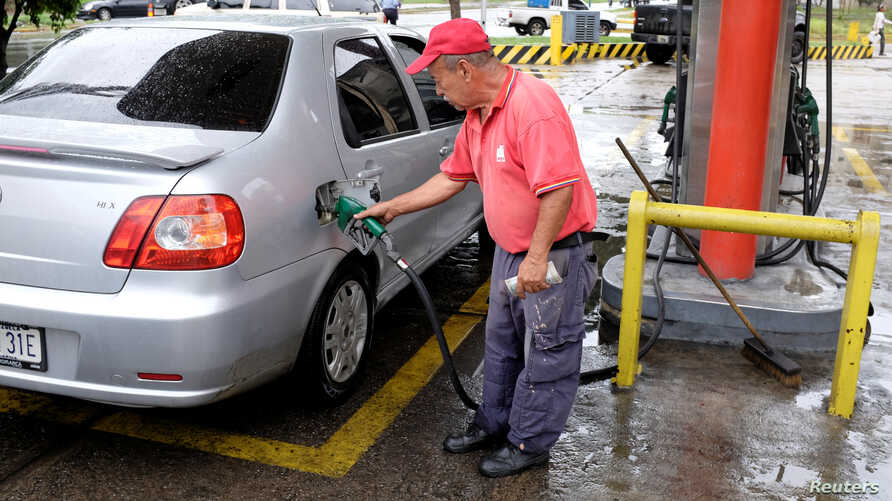 A gas station worker pumps gas into a car at a gas station of the Venezuelan state-owned oil company PDVSA in Caracas, Venezuela September 24, 2018.