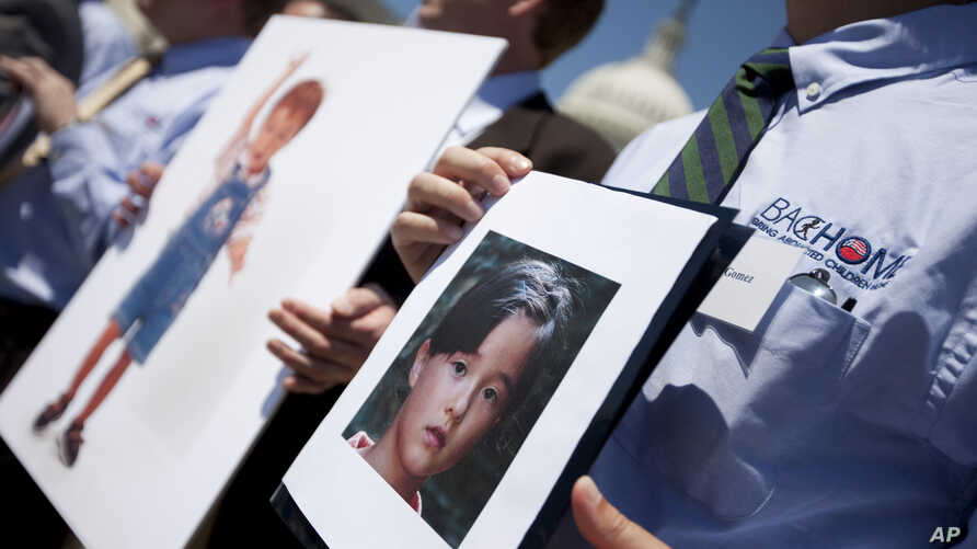 FILE - Fathers who lost their children to spousal abduction to Japan hold photos of their children during a news conference on Capitol Hill in Washington, May 5, 2010  In 2013, Japan's parliament approved joining the 1980 Hague Convention on internat