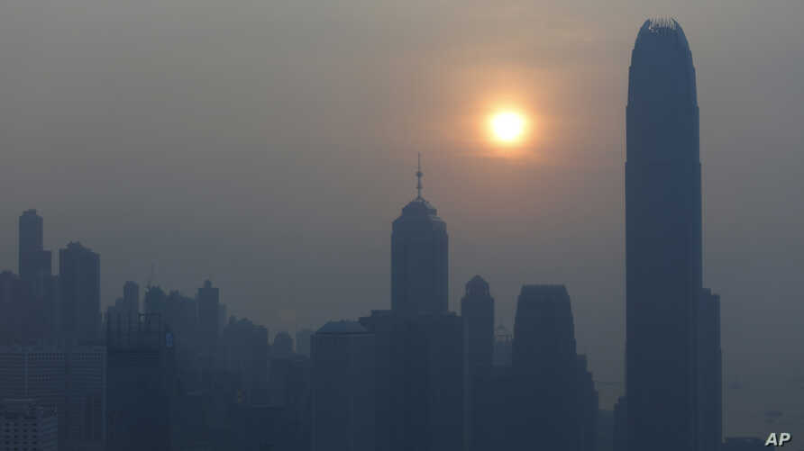 FILE - The skyline of the business district is silhouetted at sunset in Hong Kong.