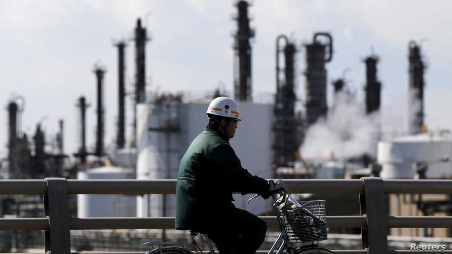FILE - A worker cycles near a factory at the Keihin industrial zone in Kawasaki, Japan, Feb. 17, 2016. A survey released Tuesday showed 83 percent of private equity firms are concerned about the impact climate change could have on the businesses they