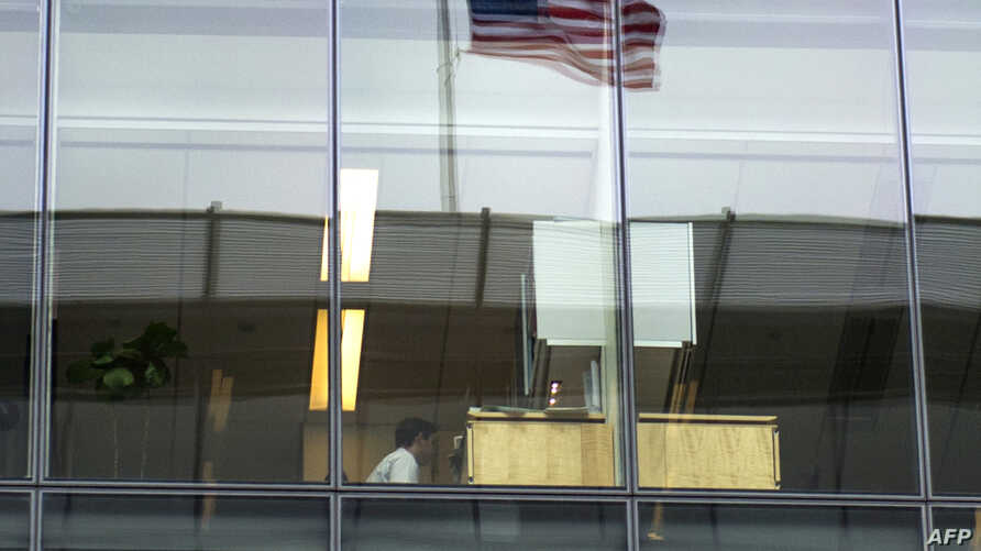 FILE - This file photo taken on May 05, 2016 shows  an office worker sitting at his desk at a bank in Washington, DC. US employers added 287,000 jobs in June, a strong rebound from May's unnerving plunge in hiring, delivering a fresh sign of US econo