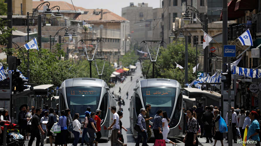 FILE - Pedestrians cross a street next to the light rail trams in Jerusalem May 11, 2017. Rights groups are criticizing the involvement of French companies in the building of another tram that connects to Israeli settlements.