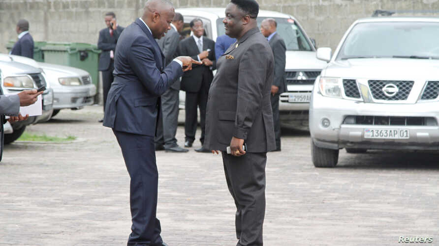 Congolese opposition Union for the Congolese Nation (UNC) president Vital Kamerhe (L) talks to opposition party Reformist Forces for Union and Solidarity's (FONUS) Joseph Olenga Nkoy at a break during talks between the opposition and the government o