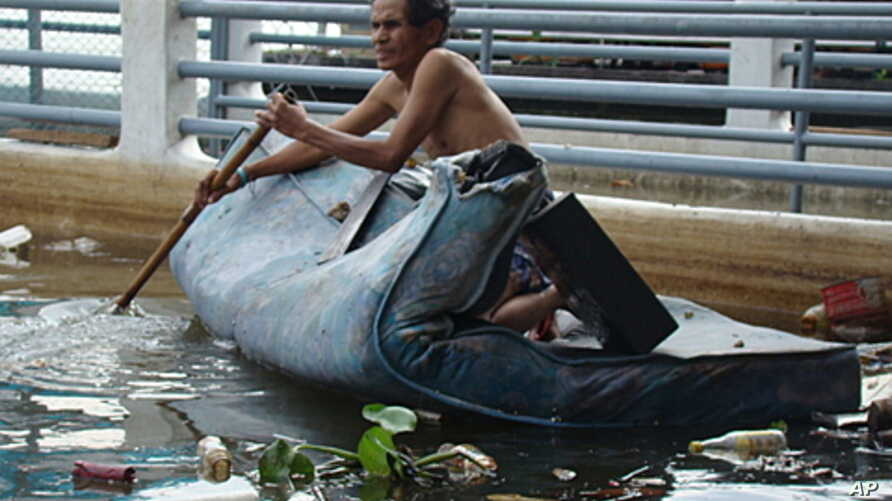 A Thai man on a mattress paddles along the Chao Phraya River which runs through Bangkok, Thailand, Nov 03, 2011.