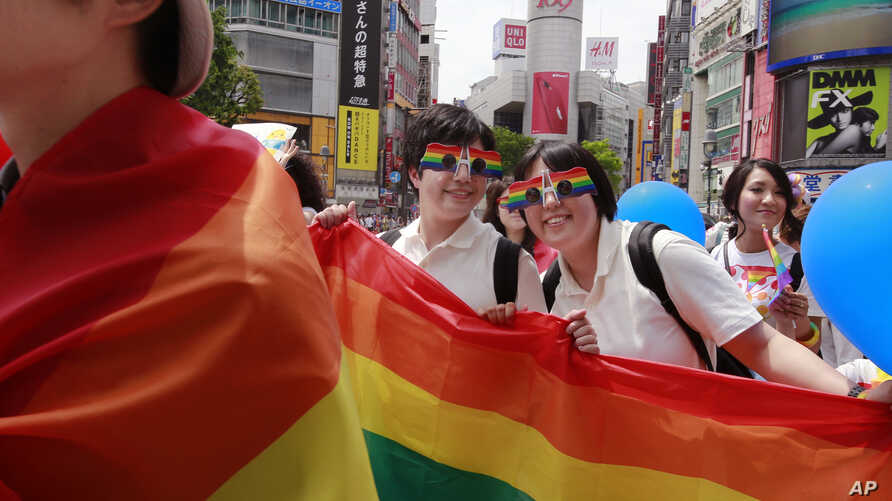 FILE - Participants smile as they march with a banner during the Tokyo Rainbow Pride parade celebrating the lesbian, gay, bisexual, and transgender (LGBT) community in Tokyo's Shibuya district, May 7, 2017.