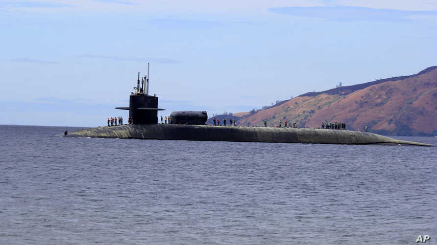 FILE - U.S. Navy crew stand on the USS Michigan, an Ohio-class guided-missile submarine, as it prepares to dock at Subic Freeport, a former US naval base west of Manila, Philippines, March 25, 2014. The sub was on a routine port call.
