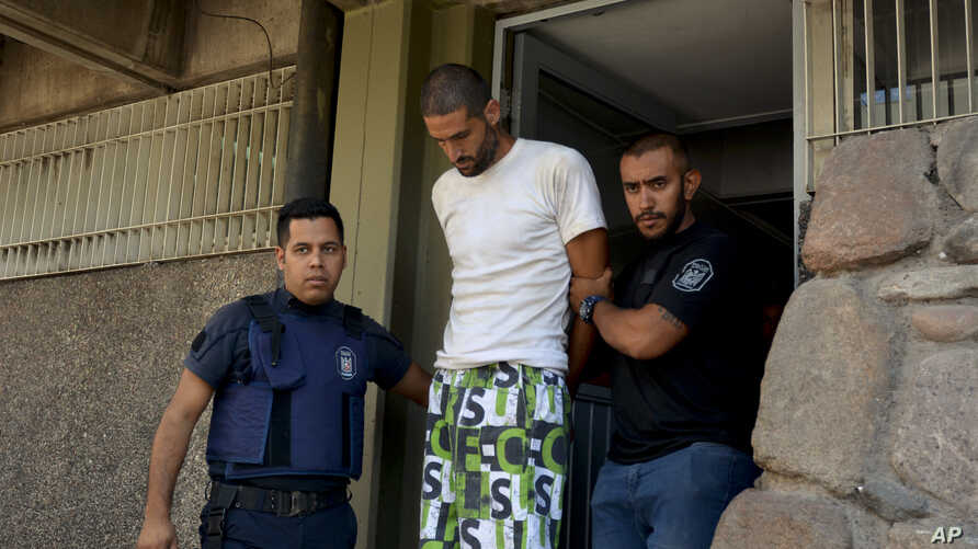 FILE - Police arrest a man in connection with a double-murder, in Mendoza, Argentina, Jan. 26, 2019.