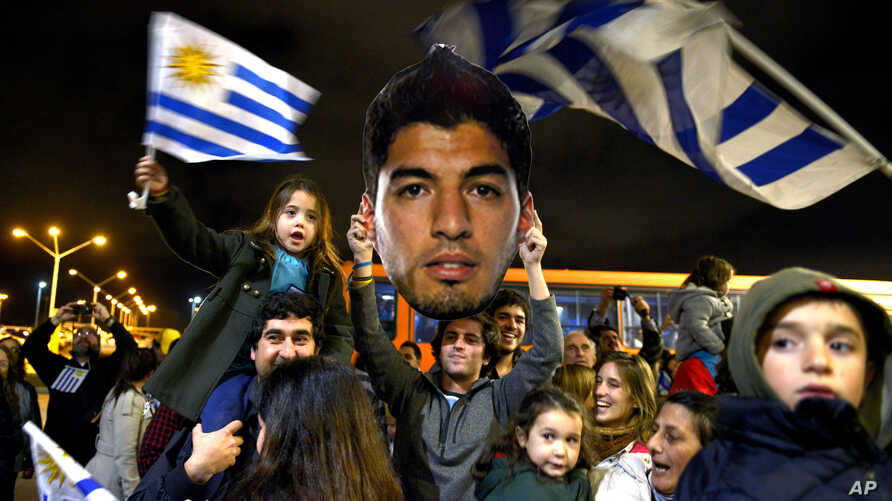 Fans of Uruguay's national soccer team await the arrival of Uruguay player Luis Suarez at Carrasco International Airport in the outskirts of Montevideo, Uruguay, June 26, 2014.