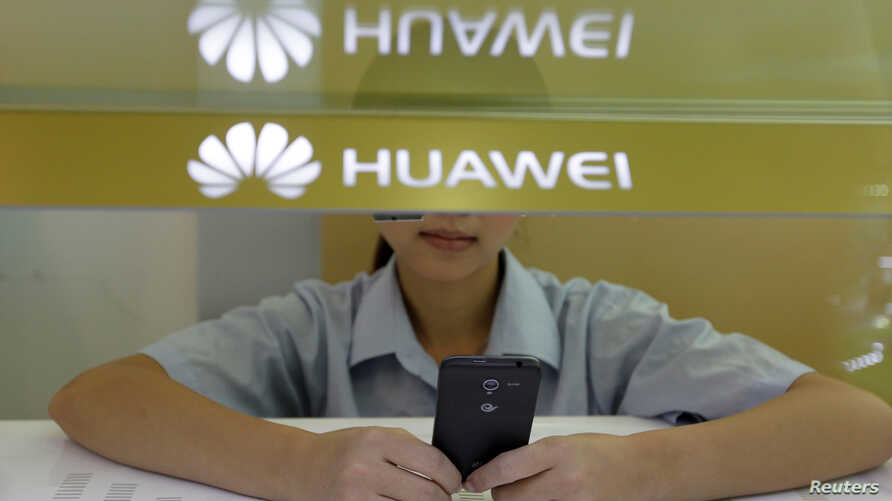 A sales assistant looks at her mobile phone as she waits for customers behind a counter at a Huawei booth in Wuhan, Hubei province, Oct. 10, 2012.
