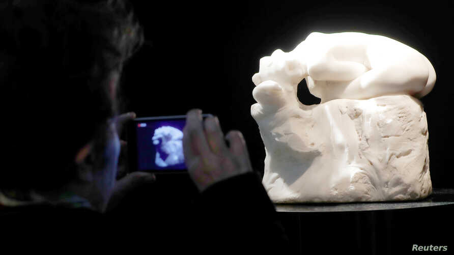"A visitor looks at ""Andromede,"" a marble by French sculptor Auguste Rodin (1840-1917) displayed at the auction house Artcurial in Paris, France, March 17, 2017."