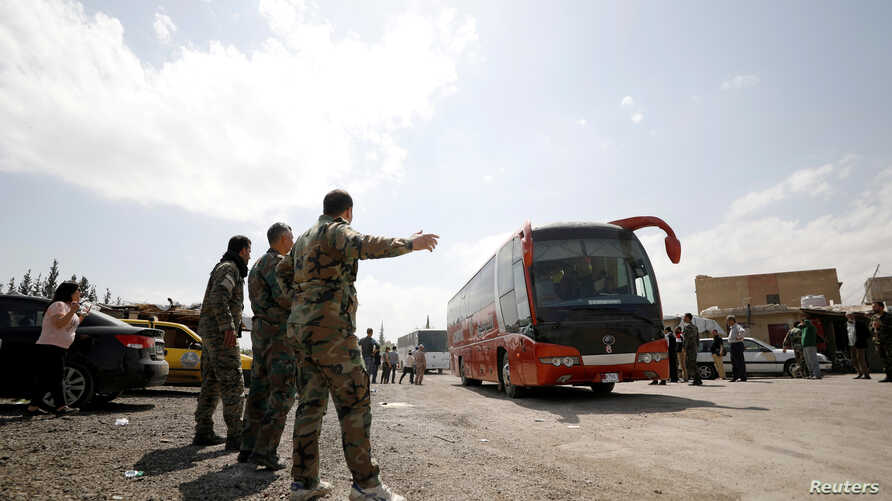 Syrian rebels and their families leave in a bus from a camp on the edge of Douma, April 9, 2018.