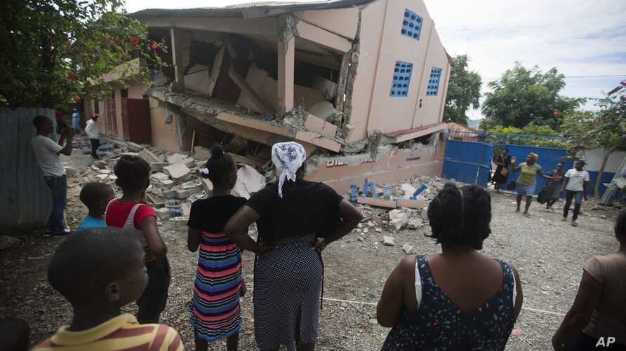Residents stand looking at a collapsed school damaged bya magnitude 5.9 earthquake the night before, in Gros Morne, Haiti, Oct. 7, 2018.