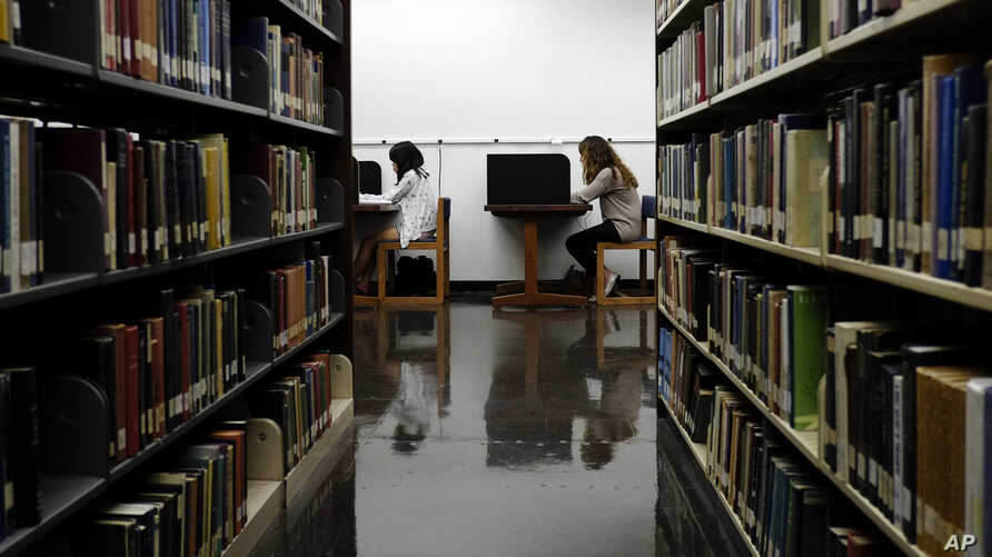 "FILE - Students are seen studying in a library on the campus of California State University in Long Beach, California, Oct. 19, 2012. Advocates of the ""gap year"" say it helps young people gain experiences they cannot learn from books."