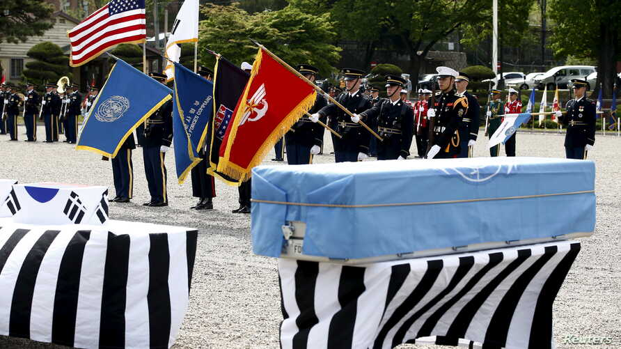 Members of the United Nations Command honor guards salute in front of boxes containing the remains of the United Nations Command (UNC) and South Korean soldiers who were killed inside North Korea in the 1950-53 Korean War during a repatriation ceremo